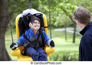 Father pushing disabled son on handicap swing - Father...