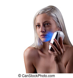 Young woman getting face phototherapy treatment by blue...