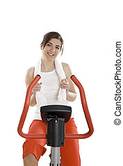 Gym exercise - Young woman training on exercise bike at the...