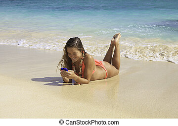 blond in bikini texting on the beach - beautiful blond in...