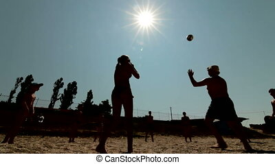 Beach Volleyball - Group of friends plays volleyball on the...