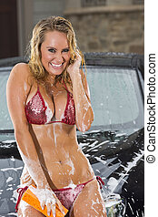 Girl Washing Car - Beautiful bikini models wash a car on a...