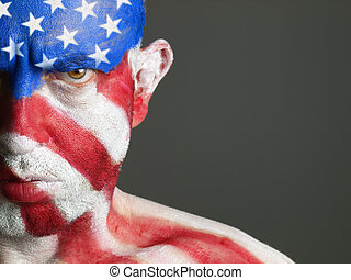 Man with his face painted with the flag of USA. The man is...