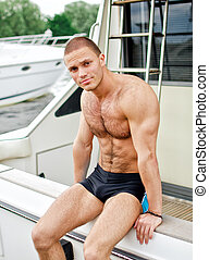 Muscular handsome sailor on his yacht.