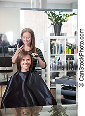 Stylist Drying Woman's Hair - Stylist drying woman's hair in...