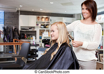 Hairdresser Curling Customer's Hair - Stylist curling womans...
