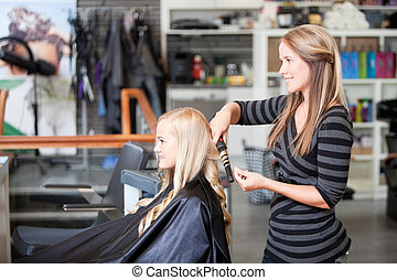 Stylist Curling Womans Hair - Stylist curling womans hair in...