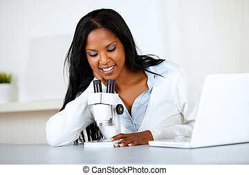 Attractive african woman working with a microscope -...