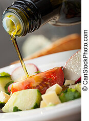 pouring olive oil over salad