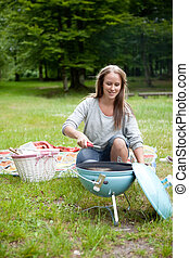 Young Woman Lighting a Barbecue