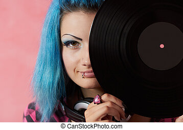 Punk girl DJ with dyed turqouise hair - Her appearance shows...