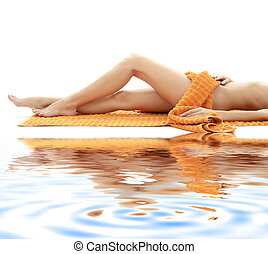long legs of relaxed lady with orange towel on white sand 4...