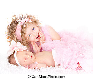 A toddler girl with her infant sister