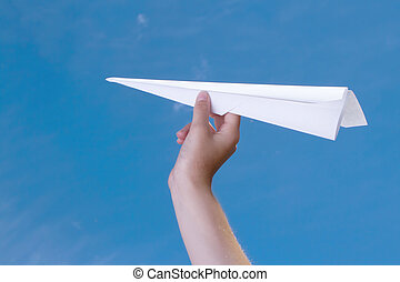 child holding a paper airplane agains a blue sky