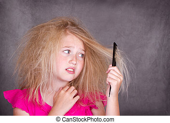 Girl with crazy tangled hair trying to comb it out
