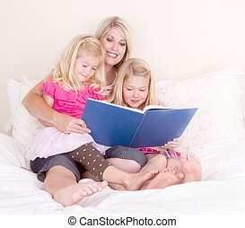 Family on bed reading book