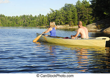 Paddling Through Calm Water - A male and female canoeist...