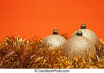 shiny christmas balls with tinsel over orange background