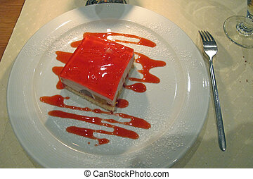 delicious cake with strawberry cream over red served at the restaurant