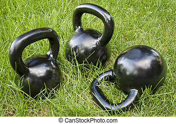 heavy kettlebells in grass - three heavy iron kettlebells in...