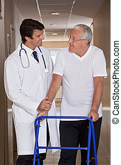 Doctor helping Patient use Walker - A doctor assisting a...