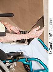 Woman on Wheelchair Using Laptop - Close-up of woman on...