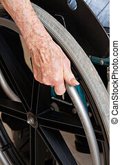 Hand On Wheelchair - Close-up of hand on the wheel of a...