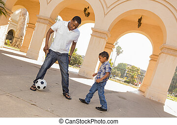 Mixed Race Father and Son Playing Soccer in the Courtyard -...