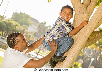 Happy Mixed Race Father Helping Son Climb a Tree in the Park...