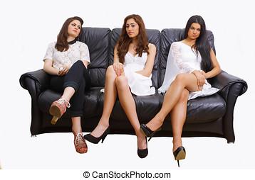Three women - Three pretty women sitting on a leather sofa