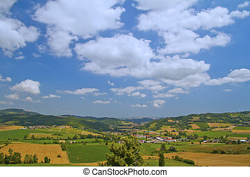 Landscape of country under blue sky with clouds