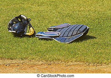 Catcher dress with mask over the grass of a baseball field