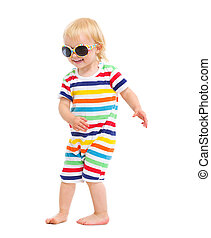 Happy baby in swimsuit and sunglasses dancing