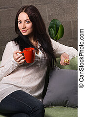 Beautiful lady drinking tea with chocolate candies