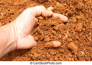 red soil - close up of hand full of red clay soil