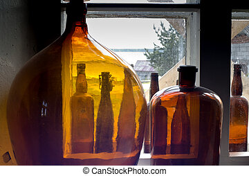 Bottles standing on windowsill show rural view - Bottles...