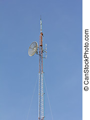 Telecommunication tower with antennas on blue sky
