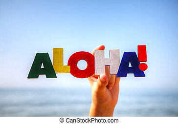 Female's hand holding colorful word 'Aloha' against blue...