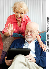 Video Chat with the Grandkids - Senior couple doing a video...