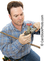 Plumber Working - Plumber using a pipe wrench to repair a...