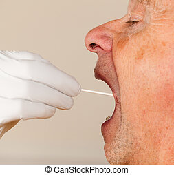 DNA swab of saliva taken from senior man - Gloved hand...