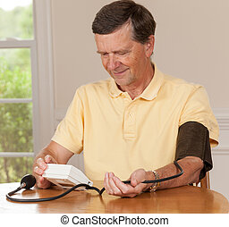 Senior man taking blood pressure at home - Senior caucasian...