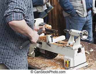 Man making wooden toy - Man carving a wooden spinning top...