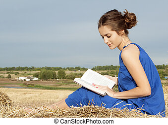 Young woman reading book outdoors on hay - 25 years old...