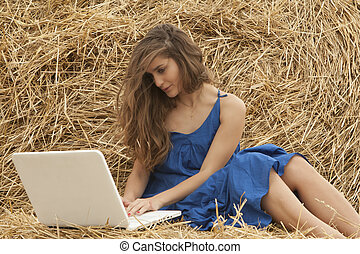 girl in blue dress typing on laptop - brunette long-haired...