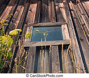old barn window with intact glass - an old weathered barn...