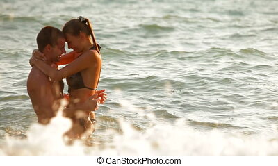 Couple Having Fun On The Beach - Happy young couple enjoying...