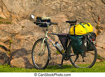 Loaded touring bicycle on rest break, next to a mauntain