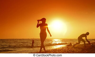 Summer Beach Fun at Sunset - Young couple playing volleyball...