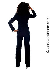 Rear view portrait of confused businesswoman looking at...